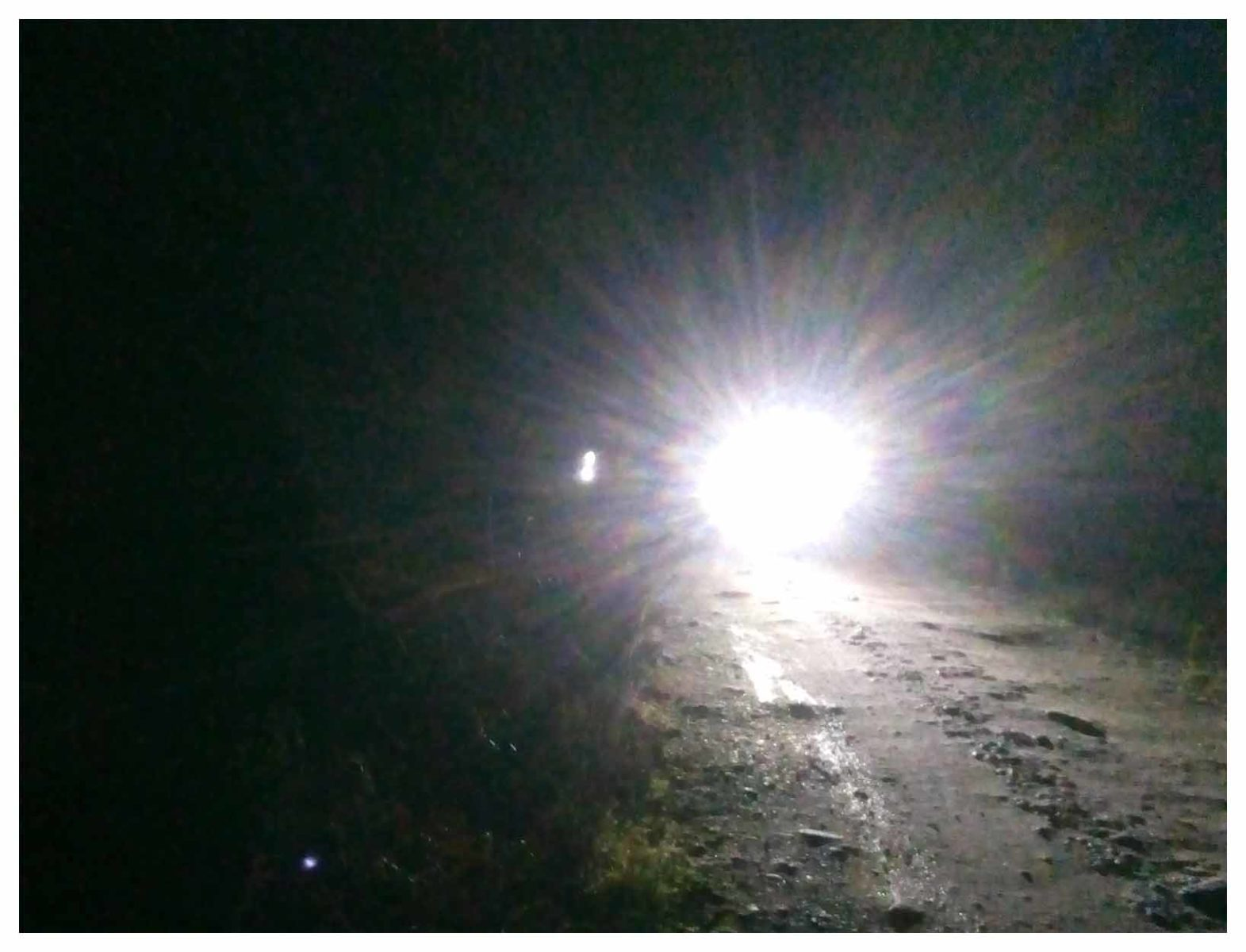 Image of cyclist in the dark with bright headlights